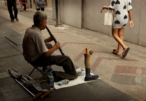 A man plays a flute for alms beside his artificial leg on a roadside as people pass by, in Bangkok, Thailand, Thursday, May 27, 2010. (AP Photo/ Manish Swarup)