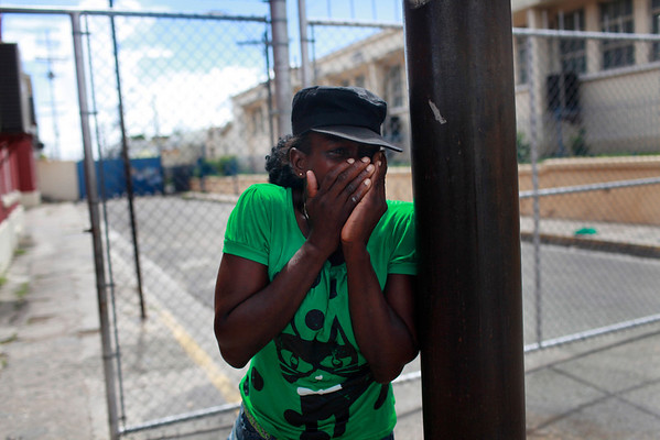 Ann Luis Marie Johnson, cries a block away from the city morgue after receiving news that her cousin's son, who was a soldier,  was killed by gang members during military operations in Kingston, Wednesday, May 26, 2010. (AP Photo/Rodrigo Abd)