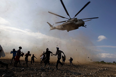 People run as a U.N. helicopter takes off after picking up peacekeepers near a makeshift camp for earthquake survivors in Port-au-Prince, Thursday, Feb. 11, 2010. Thousands are living in rudimentary shelters after Haiti's Jan. 12 powerful earthquake left the city in ruins. (AP Photo/Ramon Espinosa)