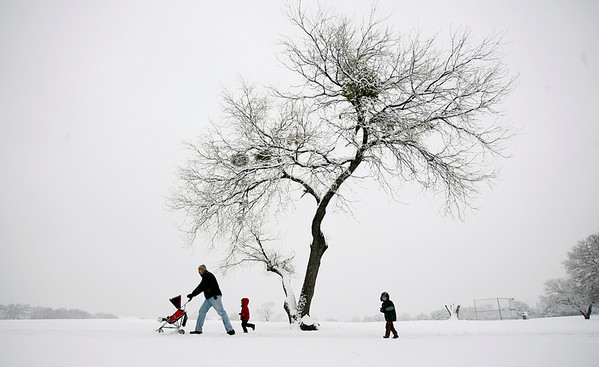 Jared Orr  walks in the snow with his children, from left, 9 month-old Jude, Daniel, 4, and Abraham, 5, in Veterans Park in Arlington, Texas on Thursday, Feb. 11, 2010.  (AP Photo/Fort Worth Star-Telegram/Ian McVea) MANDATORY CREDIT