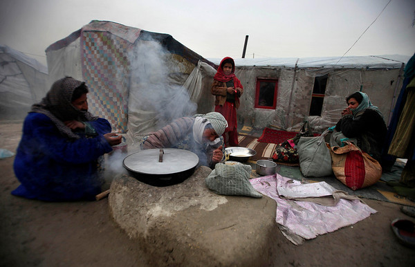 An internally displaced Afghan family from Mazar-e Sharief do daily chores outside their impoverished shanty at a refugee camp on a cold day in Kabul, Afghanistan, Thursday, Feb. 11, 2010 (AP Photo/Altaf Qadri)