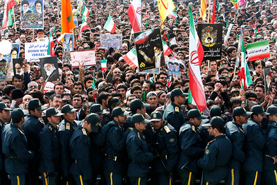 Police officers stand guard as pro-government Iranian demonstrators attend a rally commemorating the anniversary of the 1979 Islamic Revolution, at the Azadi (Freedom) Sq. in Tehran, Iran, Thursday, Feb. 11, 2010. Authorities banned foreign media in Iran from covering the pro-reform protests, while allowing them to cover the official anniversary ceremonies, including Ahmadinejad's speech, but there is a ban on covering opposition protests.  (AP Photo/Vahid Salemi)