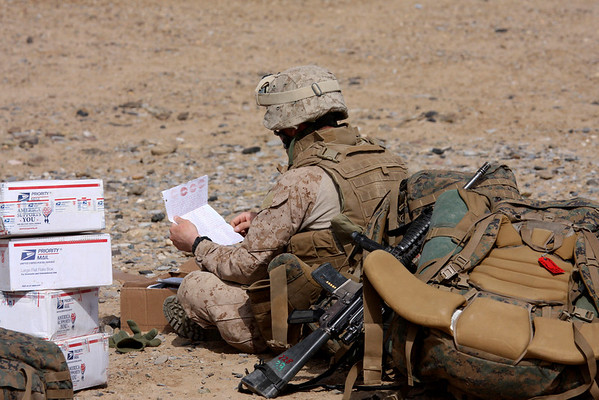A service man from the U.S. 3rd Battalion, 6th Marines regiment reads a letter covered in lipstick kisses at his front line outpost on Thursday, Feb. 11, 2010, on the outskirts of Marjah, Afghanistan, where NATO commanders are planning a major offensive against the Taliban in the coming days. (AP Photo/Alfred de Montesquiou.)