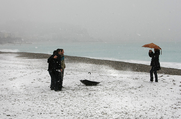 Tourists take photographs on a beach as snow falls in Nice, southeastern France, Thursday, Feb. 11, 2010. (AP Photo/Lionel Cironneau)