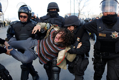 A protester is carried away by police outside a convention center in Ciudad Juarez, Mexico, Thursday, Feb. 11, 2010.  Protesters demanded the president resign after a recent massacre that killed 15 teenagers with no known gang ties. (AP Photo/Alexandre Meneghini)