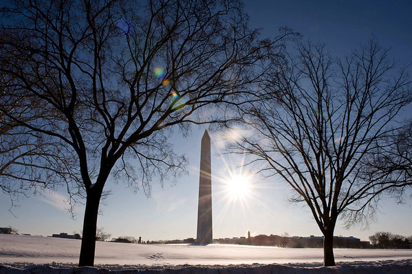 The sun shines on the snow covered ground of the Washington Monument in Washington, Thursday, Feb. 11, 2010. The Washington area began cleaning up, a day after a another snow storm hit the area. (AP Photo/Cliff Owen)
