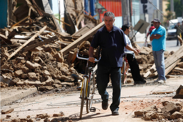 A resident pushes a bike along a street in downtown Talca, 160 miles south of Santiago, Saturday, Feb. 27, 2010. An 8.8-magnitude earthquake struck central Chile early Saturday. The quake hit 200 miles  southwest of the capital.. (AP Photo/Roberto Candia)