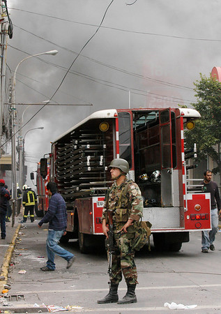 A soldier stands next to a firefighter truck in Concepcion, Chile, Monday, March 1, 2010. The government sent soldiers to Concepcion and ordered a nighttime curfew to quell looting after an 8.8-magnitude earthquake struck central Chile early Saturday. (AP Photo/Ricardo Pasten)