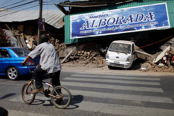 A resident looks at a destroyed building in downtown Talca, Chile, Saturday, Feb. 27, 2010, after an 8.8-magnitude struck central Chile. (AP Photo/Roberto Candia)