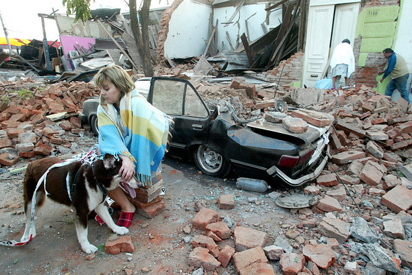 A woman sits in front a quake-damaged house in Talca, Chile, after a 8.8-magnitude earthquake struck the country early Saturday, Feb. 27, 2010. (AP Photo/Sebastian Martinez)