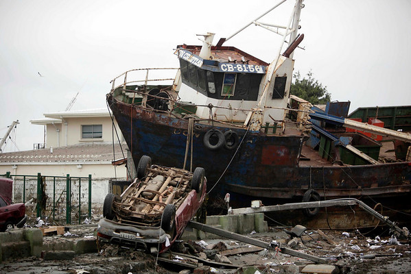 A boat lies marooned near the coast on top of a car in Talcahuano, Chile, Monday, March 1, 2010. Chile's central coast was hit first with an 8.8-magnitude earthquake early Saturday, then with a tsunami, causing widespread damage.  (AP Photo/ Natacha Pisarenko)