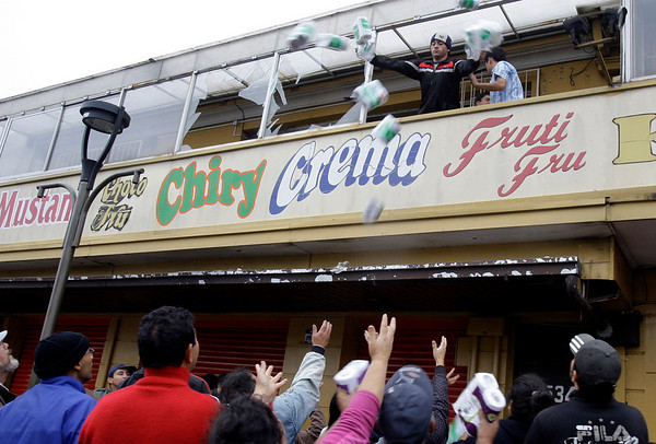 A man throws goods from a window as a market is looted in Concepcion street, Chile, Monday, March 1, 2010. Security forces said they arrested dozens of people for violating an anti-looting curfew.  (AP Photo/Natacha Pisarenko)