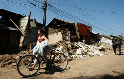 A woman passes a damaged home in Curico, Chile, Monday, March 01, 2010.  (AP Photo/Fernando Vergara)