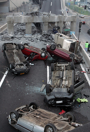 Vehicles that were driving along a highway that collapsed during the earthquake near Santiago are seen overturned  on the asphalt Saturday Feb. 27, 2010, ( AP Photo/David Lillo)