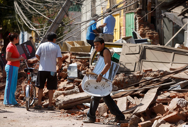 A resident recovers items from the rubble in downtown Talca, Chile, Saturday, Feb. 27, 2010,  after an 8.8-magnitude struck central Chile. (AP Photo/Roberto Candia)