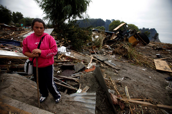Paola Gajardo, 30, looks down at the remains of her destroyed house in Constitucion, Chile, Monday, March 1 , 2010. (AP Photo/ Roberto Candia)