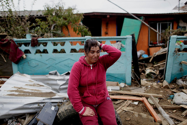Victoria Hernandez cries outside her parents house in Dichato, Chile, Monday, March 1, 2010. Hernandez believes her parents are alive though they remain missing. An 8.8-magnitude earthquake struck central Chile early Saturday causing widespread damage. (AP Photo/ Natacha Pisarenko)
