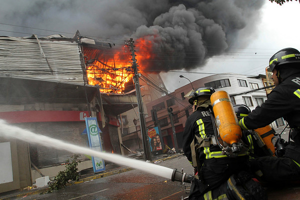 Firemen try to put out a fire on a shop in Concordia, Chile, Monday, March 1, 2010. (AP Photo/ Ivan Pisarenko)
