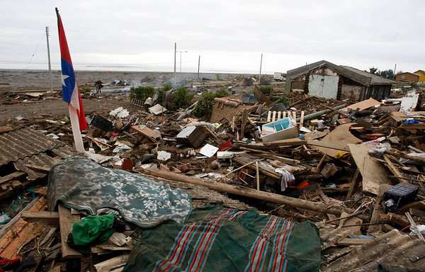 A Chilean flag stands amid debris in Iloca, Chile, Monday, March 1, 2010. (AP Photo/Fernando Vergara)