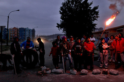People stand outside their homes, guarding them from looters in Concepcion, Chile, Monday, March. 1, 2010. The government sent soldiers to Concepcion and ordered a nighttime curfew to quell looting after an 8.8-magnitude earthquake struck central Chile early Saturday. (AP Photo/Natacha Pisarenko)