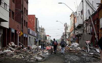 People walk through a damaged neighborhood in Talcahuano, Chile, Monday, March 1, 2010. Chile's central coast was hit first with an 8.8-magnitude earthquake early Saturday, then with a tsunami, causing widespread damage.  (AP Photo/Natacha Pisarenko)