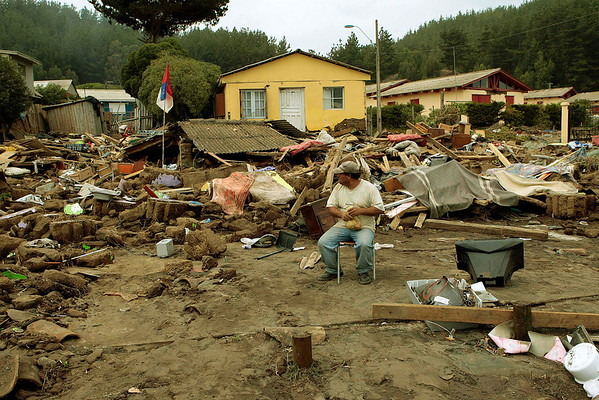 A man sits next to his belongings in Iloca, Chile, Monday, March 1, 2010. (AP Photo/Luis Hidalgo)