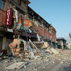 A resident takes photos of a building damaged in Talca, Chile, Saturday, Feb. 27, 2010. (AP Photo/Sebastian Martinez)