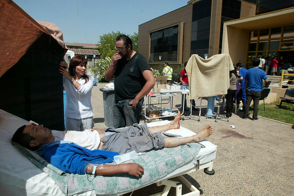 A patient lies on a hospital bed outside a hospital in Talca, Chile, Saturday, Feb. 27, 2010, after an 8.8-magnitude struck central Chile. The epicenter was 70 miles from Concepcion, Chile's second-largest city. (AP Photo/Sebastian Martinez)