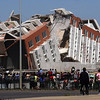 Residents look at a collapsed  building in Concepcion, Chile, Saturday Feb. 27, 2010 after an 8.8-magnitude struck central Chile. (AP Photo)