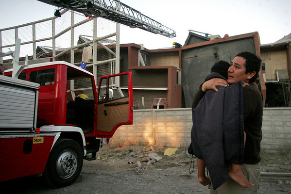 A man carries a child next to a damaged building in Concepcion, Chile, Saturday Feb. 27, 2010. (AP Photo)