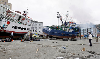 Boats lie marooned near the coast in Talcahuano, Chile, Monday, March 1, 2010. An 8.8-magnitude earthquake struck central Chile early Saturday triggering a tsunami that hit coastal communities. (AP Photo/ Natacha Pisarenko)