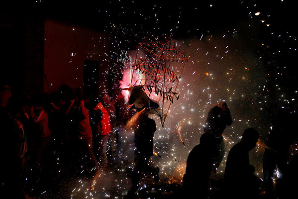 A reveler, carrying a bull's head made of cardboard, takes part in carnival celebrations amidst exploding fireworks as people get out of his way in Zapotitlan, outskirts of Mexico City, Sunday, Feb. 14, 2010. (AP Photo/Eduardo Verdugo)