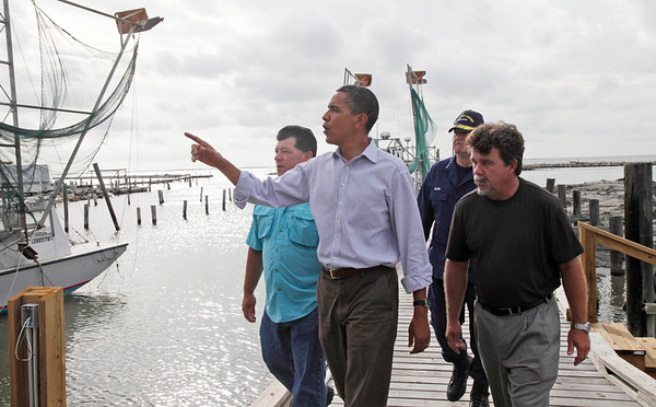 President Barack Obama walks past fishing boats on a pier with Mayor of Grand Isle David Camardelle, right, National Incident Commander Adm. Thad Allen, second right, and Chris Camardelle after a visit to Camardelle's, a live bait and boiled seafood restaurant shop, to meet with residents regarding the BP Gulf Coast oil spill in Grand Isle, Louisiana, Friday, June 4, 2010. (AP Photo/Charles Dharapak)