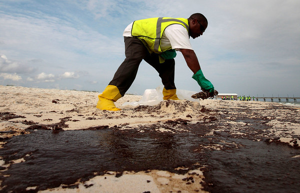 Steve Gardner of Mobile scrapes oil from the sand along a 700-yard long strip of oil that washed up on the beach in Gulf Shores,  Ala., Friday, June 4, 2010. Oil from the Deepwater Horizon disaster has started washing ashore on the Alabama and Florida coast beaches. (AP Photo/Dave Martin)