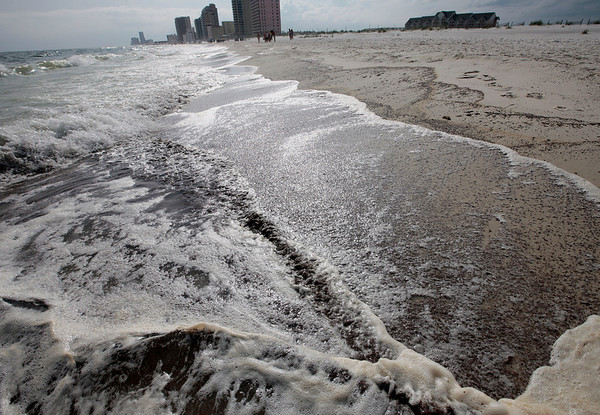 Oil in the surf washes up on a 700-yard long strip of beach in Gulf Shores, Ala., Friday, June 4, 2010. Oil from the Deepwater Horizon disaster has started washing ashore in sheets on the Alabama and Florida coast beaches. (AP Photo/Dave Martin)