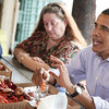 President Barack Obama eats a shrimp as he sits next to convenience store owner Patti Rigaud as he visits Camardelle's, a live bait and boiled seafood restaurant shop, to meet with residents regarding the BP Gulf Coast oil spill in Grand Isle, La., Friday, June 4, 2010. (AP Photo/Charles Dharapak)