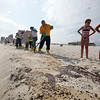 Workers hired by BP shovel oil and sand along a 700-yard long strip of oil that washed up on the beach in Gulf Shores, Ala., Friday, June 4, 2010. Oil from the Deepwater Horizon disaster has started washing ashore on the Alabama and Florida coast beaches. (AP Photo/Dave Martin)