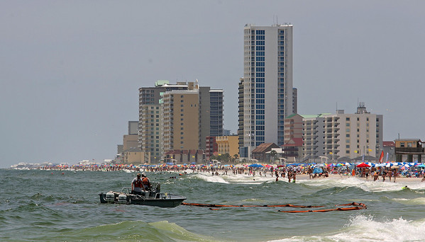 A work boat tries to use a boom to contain a pool of oil in the waters off Gulf Shores, Ala. Friday, June 4, 2010. Large globs of oil began washing ashore in Gulf Shores Friday. (AP Photo/Press-Register, Bill Starling)
