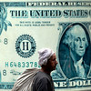 An Egyptian walks in front of a giant poster for the U.S dollar at an exchange office in Cairo, Egypt, Sunday, Feb. 14, 2010. The US dollar rose to a 9-month high against the euro Friday, Feb. 12, 2010, as worries about bank lending curbs in China and European debt woes drove investors to safe havens like the dollar. (AP Photo/Amr Nabil)