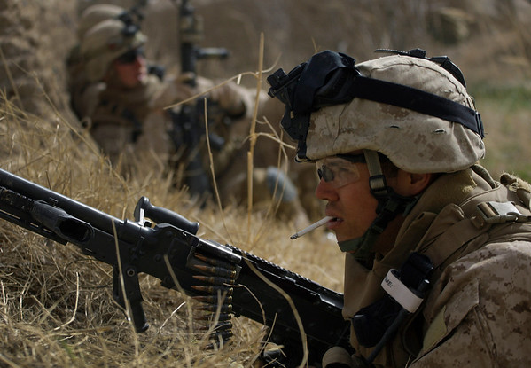 U.S. Marines from 3rd Battalion, 6th Marine Regiment take cover during a firefight as Taliban snipers fire on their position in Marjah in Afghanistan's Helmand province on Sunday Feb. 14, 2010. (AP Photo/David Guttenfelder)