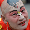 A performer with a tiger sticker displayed on his face dances on the first day of Lunar New Year celebrations at the Qianmen in Beijing, Sunday, Feb. 14, 2010. Millions of Chinese celebrated the Lunar New Year of the Tiger which began on Sunday. (AP Photo/Andy Wong)