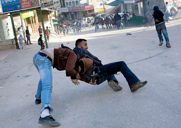 A Palestinian rioter tries to grab a weapon from a plain-clothes Israeli police officer, right, during clashes in Shuafat refugee camp in east Jerusalem, Tuesday, Feb. 9, 2010. (AP Photo/Bernat Armangue)
