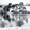 A trout fisherman casts his line in his boat at Langley Dam, England, as a fresh blast of wintry weather hit Britain, bringing more snow and icy conditions on Tuesday Feb. 9, 2010.    (AP Photo / Owen Humphreys, PA)