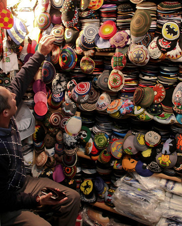 An Israeli man sits in his stall where he sells skull caps in downtown Jerusalem, Tuesday, Feb. 9, 2010. (AP Photo/Tara Todras-Whitehill)