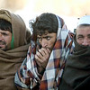 Afghans cover themselves as they wait to be evacuated Tuesday, Feb. 9, 2010, after an avalanche struck the Salang Pass, Afghanistan. (AP Photo/Altaf Qadri)