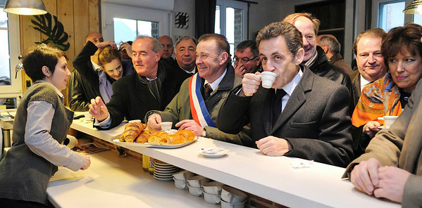French President Nicolas Sarkozy enjoys a cup of coffee Tuesday Feb. 9, 2010 in Souday, central France, during a visit focusing on the rural territories ' future. (AP Photo /Eric Feferberg; Pool)