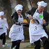 Lord Alfred Dubs, right, British Labour Party politician and former Member of Parliament and Allegra Stratton, center, of The Guardian newspaper compete in the annual Parliamentary Pancake Race in Westminster, London, along with other journalists, MPs and members of the House of Lords, to raise money for the charity 'Rehab' and to raise awareness of it's work for people with disabilities Tuesday Feb. 9, 2010.    (AP Photo/Stefan Rousseau/PA Wire)
