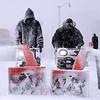 Ricki Ghani, left, and Eric Brannon clear snow from sidewalks around Festival Hall Park in Racine, Wis. as snow sweeps across southeastern Wisconsin Tuesday Feb. 9, 2010.  (AP Photo/Journal Times, Mark Hertzberg)