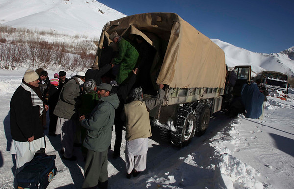 Afghans get into an army truck Tuesday Feb. 9, 2010, after being evacuated from the avalanche which struck the Salang Pass, Afghanistan. Officials said the avalanches have killed at least 28 people and left another 1,500 stranded in a snow-blocked mountain pass, with the Defense Ministry releasing a statement saying another 70 people have been injured as rescue efforts continued to dig out hundreds of vehicles stuck on the pass north of Kabul.(AP Photo/Altaf Qadri)