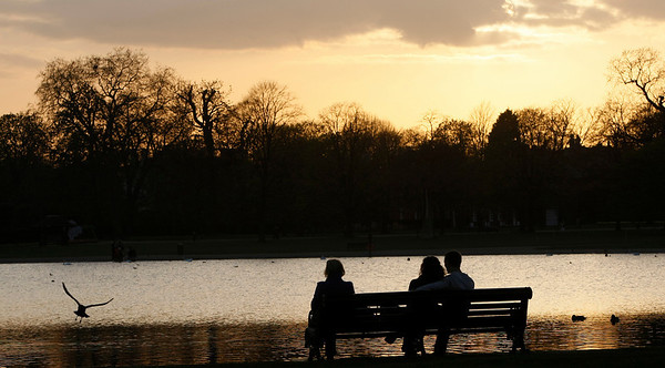 Three people watching the sunset in London's Kensington Gardens, Friday, April, 16, 2010. There are airplane-free skies Friday as most of Britain's airports remain closed due to a cloud of volcanic ash in the upper atmosphere above much of Europe, emanating from a volcanic eruption near the Eyjafjallajokull glacier in Iceland. The volcanic ash is a hazard to jet aircraft engines, causing the cancellation of many flights over European airspace.(AP Photo/Alastair Grant)